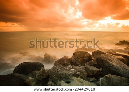 Bad weather. Stormy weather on the stone coast during a fiery orange sunset. Rain on the horizon. Long exposure - stock photo