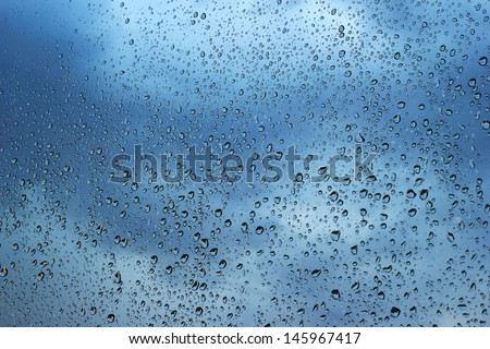 Bad weather. Water drops on window with dark clouds in the background