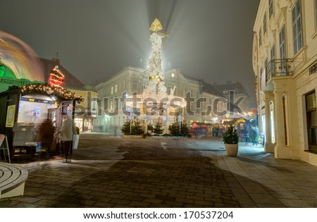 BADEN, AUSTRIA - DECEMBER 23: Plague column illuminated for Christmas on December 23, 2013 in Baden. Baden is a spa town in the Austrian state of Lower Austria and the capital of the Baden district. - stock photo