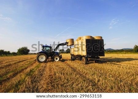 BADEN BADEN, GERMANY - CIRCA JULY 2007 - Tractor impales on straw bales and loads the bales on the trailer