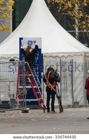 BADEN, SWITZERLAND. November 2nd, 2015. Alstom logos being removed by worker to install GE logos for merger and acquisition of General Electric. - stock photo