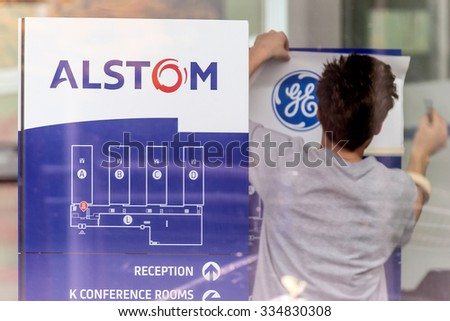 Baden, Switzerland. 31st October 2015. Alstom logos being removed by worker to install GE logos before merger and acquisition of General Electric on 2nd November 2015. - stock photo