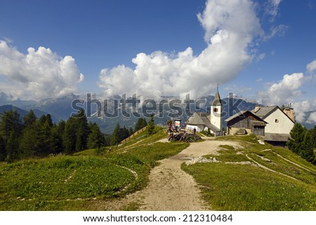BADIA, ITALY-AUGUST 03, 2014: mountain rocky path with mountain hut and church on the Dolomites Sasso della Croce, in Badia.