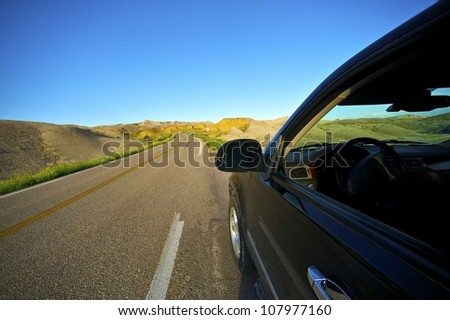Badlands Drive Thru. Traveling Theme with Black SUV on the Loop Road in Badlands National Park, South Dakota, USA. - stock photo