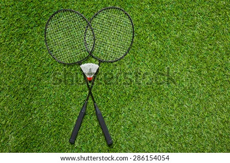 Badminton rackets with shuttlecock on the grass
