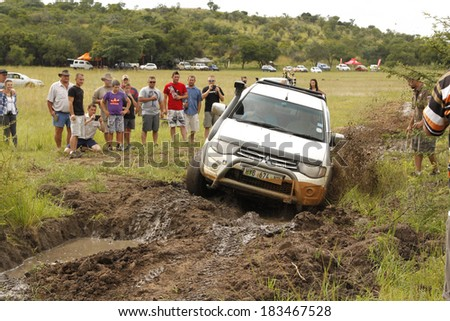 BAFOKENG - MARCH 8: White Toyota Triton DHD crossing mud obstacle at Leroleng 4x4 track on March 8, 2014 in Bafokeng, Rustenburg, South Africa