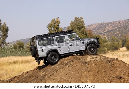 BAFOKENG - MAY 18: Silver Land Rover Defender 110 SW scaling high sand dune obstacle at new 4x4 track opening event May 18, 2013 in Bafokeng, Rustenburg, South Africa   - stock photo