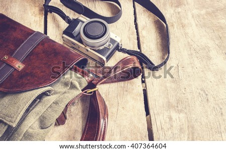 bag and retro camera on vintage wooden table background, traveling holiday photography concept - stock photo
