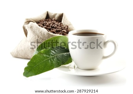 Bag full of coffee beans with green leaves and coffee cup on white - stock photo