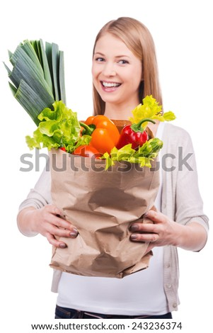 Bag full of vitamins. Beautiful young woman stretching out a shopping bag full of groceries while standing against white background