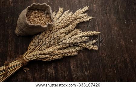 Bag full of wheat and wheat ears - stock photo