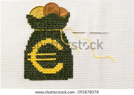 Bag of money with euro symbol embroidered green and yellow thread on white fabric. In the bag are cents. - stock photo