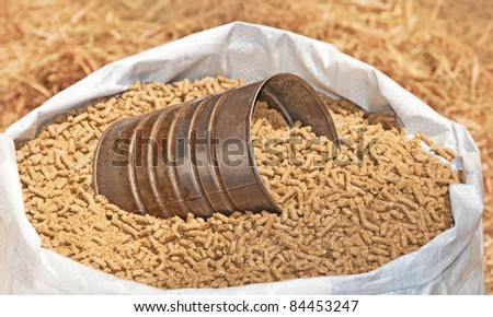 Bag of pelleted horse feed with a coffee can for measuring - stock photo