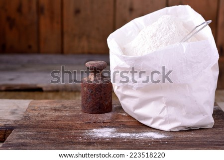Bag of whole flour on old wooden background - stock photo