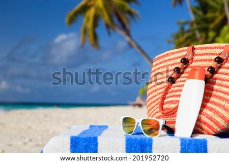 bag, sun glasses and suncream on tropical beach - stock photo