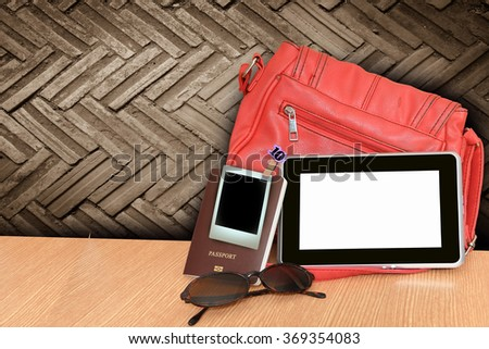 bag ,tablet and passport with dirty brick wall background