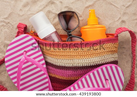 Bag with beach accessories lying on the sand of the beach, as a backdrop