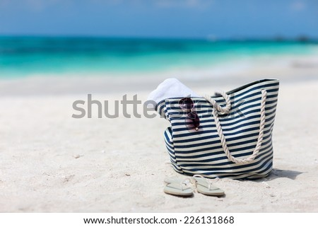 Bag with beach towel, sun glasses and flip flops on a tropical beach