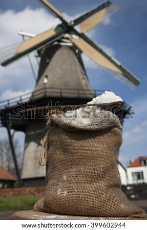 Bag with flour and a dutch windmill on the background - stock photo