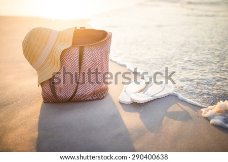 bag with sunhat and flip flop on the sand - stock photo
