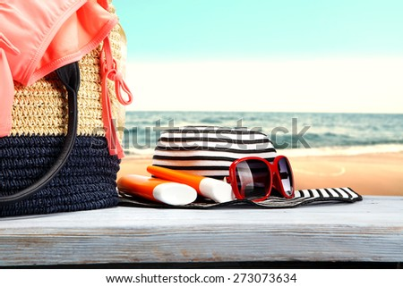 bag with swimsuit and red glasses on hat of white and blue