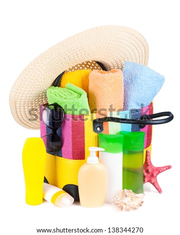 Bag with towels, sunglasses, hat and beach items. Isolated on white background
