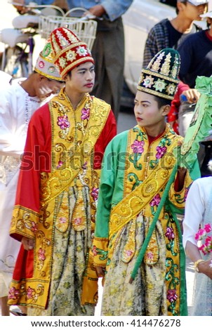 BAGAN, MYANMAR - CIRCA FEBRUARY 2007: Two young men in colorful satin costumes with face paint in a Buddhist procession