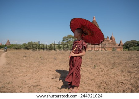 BAGAN, MYANMAR - DEC 18, 2014: novice monk with red umbrella walking around  bagan temple on December 18, 2014 in Bagan, Myanmar.  - stock photo