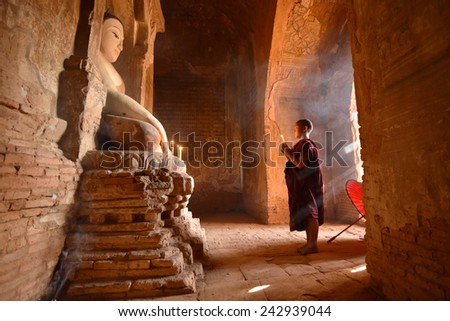 BAGAN, MYANMAR - DEC 18, 2014: Southeast Asian neophyte praying with candle light in a Buddihist temple on December 18, 2014 in Bagan, Myanmar. - stock photo