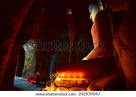 BAGAN, MYANMAR - DEC 18, 2014: Southeast Asian neophyte praying with candle light in a Buddihist temple on December 18, 2014 in Bagan, Myanmar.