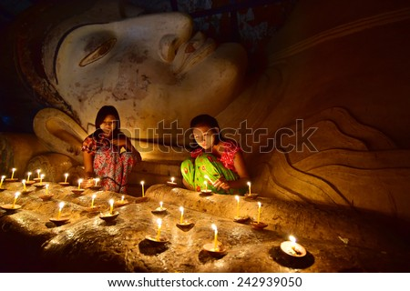 BAGAN, MYANMAR - DEC 18, 2014: Southeast Asian young girls praying with candle light in a Buddihist temple on December 18, 2014 in Bagan, Myanmar. - stock photo