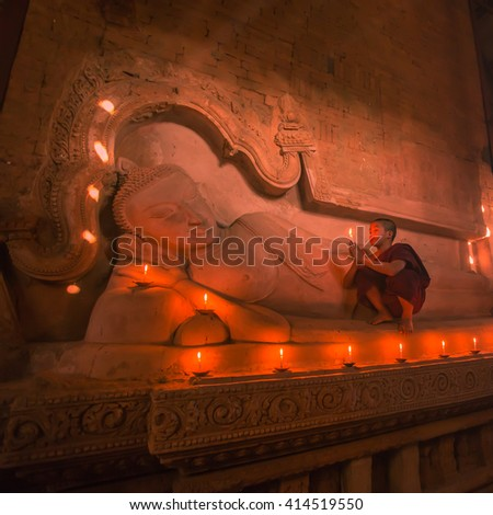 BAGAN, MYANMAR - DEC 11, 2015: Southeast Asian young little Buddhist monk praying with candle light in a Buddihist temple on December 11, 2015 in Bagan, Myanmar - stock photo