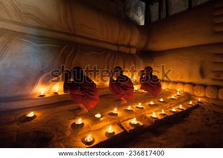 BAGAN, MYANMAR - DEC 31, 2012: Southeast Asian young little Buddhist monks praying with candle light in a Buddihist temple on December 31, 2012  in Bagan, Myanmar.