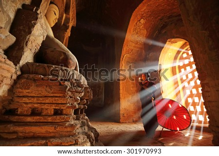 BAGAN, MYANMAR - DEC 6, 2014: Unidentified Buddhism neophyte prays in Buddihist temple on December 6, 2014 in Bagan, Myanmar. Southeast Asian neophyte praying in a Buddihist temple