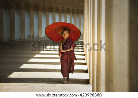 BAGAN, MYANMAR - DEC 6: Unidentified young Buddhism novice is walking and holding an umbrella at Shwezigon temple on Dec 6, 2014 in Bagan. - stock photo