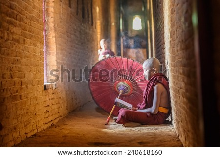 BAGAN, MYANMAR - DEC 6: Unidentified young Buddhism novices pray at Shwezigon temple on Dec 6, 2014 in Bagan. Buddhism is predominantly of the Theravada tradition, practised by 89% of the population. - stock photo
