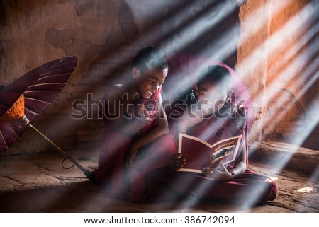 BAGAN, MYANMAR-4 FEBRUARY 2016: Burmese novices reading book inside ancient stupa with light ray background at Bagan, Myanmar.