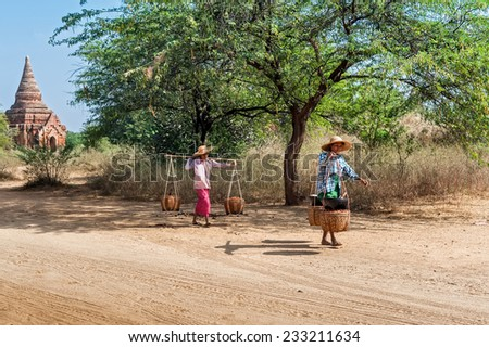 BAGAN, MYANMAR - JANUARY 16, 2014: Burmese rural women carrying baskets with berries harvest. Burma travel destinations with ancient Buddhist Temples and local people at Bagan Kingdom - stock photo