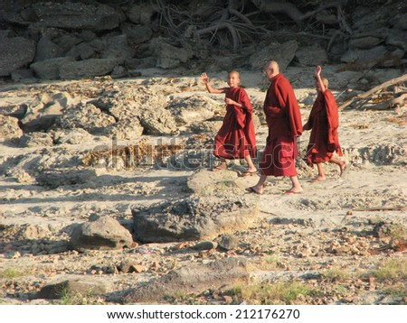 BAGAN, MYANMAR: JANUARY  2, 2010: Novice monks with their master walk on the banks of the Irrawaddy River to their Buddhist monastery. - stock photo