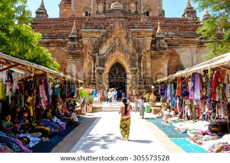 Bagan, Myanmar - June 30, 2015: Tourists and local people in front of old temple in Bagan, Myanmar in June 2015 - stock photo