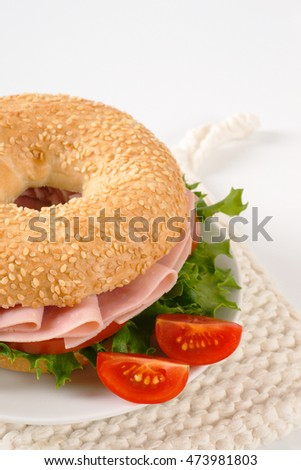 bagel sandwich with ham on white plate
