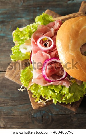 bagel with bacon and sprouts sprouts pink salt on a wooden background - stock photo