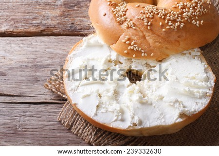 bagel with cream cheese and sesame close-up on the table. top view of the horizontal  - stock photo