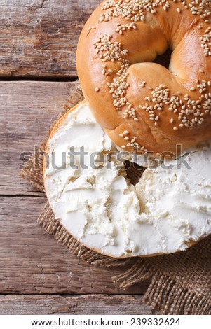 bagel with cream cheese and sesame close-up on the table. top view of the vertical  - stock photo