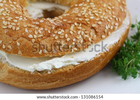 Bagel with cream cheese with watercress garnish, close up - stock photo