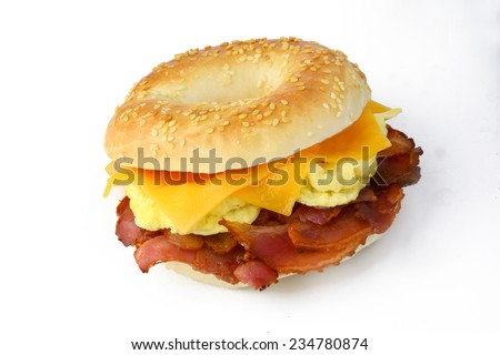 Bagel with fried bacon, scrumbled eggs and cheddar cheese. Studio isolated - stock photo