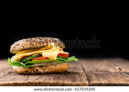 Bagel (with Gouda cheese) on vintage looking background (close-up shot; selective focus) - stock photo
