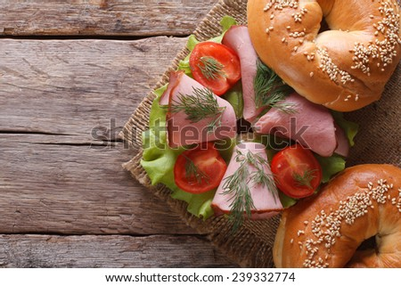 bagel with ham and vegetables on an old wooden table close-up. horizontal view from above  - stock photo