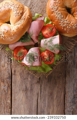 bagel with ham and vegetables on an old wooden table close-up. vertical top view  - stock photo