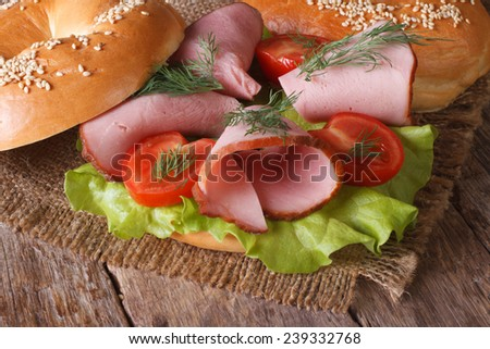bagel with ham and vegetables on wooden table close-up. horizontal  - stock photo